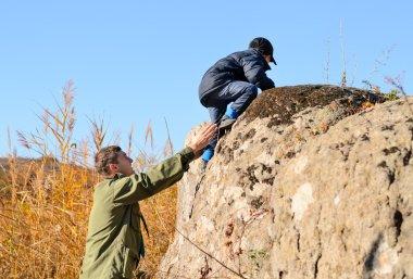 Scout helping a young boy rock climbing