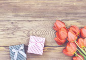 Fotografie Tulips on Wooden Table with Little Gift Boxes