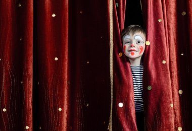 Young Boy Wearing Clown Make Up Peering Out Through Opening in Red Stage Curtains stock vector