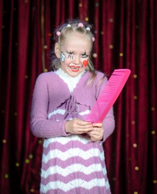 Girl Wearing Clown Make Up Holding Over Sized Comb
