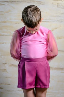 Boy Wearing Pink Dance Outfit with Head Bowed