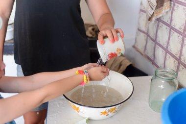 Little boy washing his hands in an enamel basin