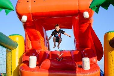 Small boy jumping in bouncy castle