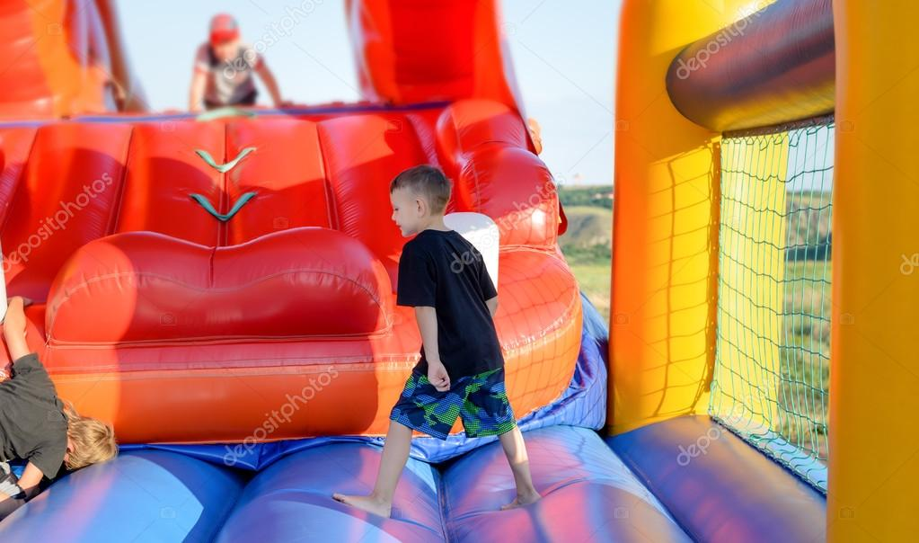 Full length of boy playing on bouncy castle