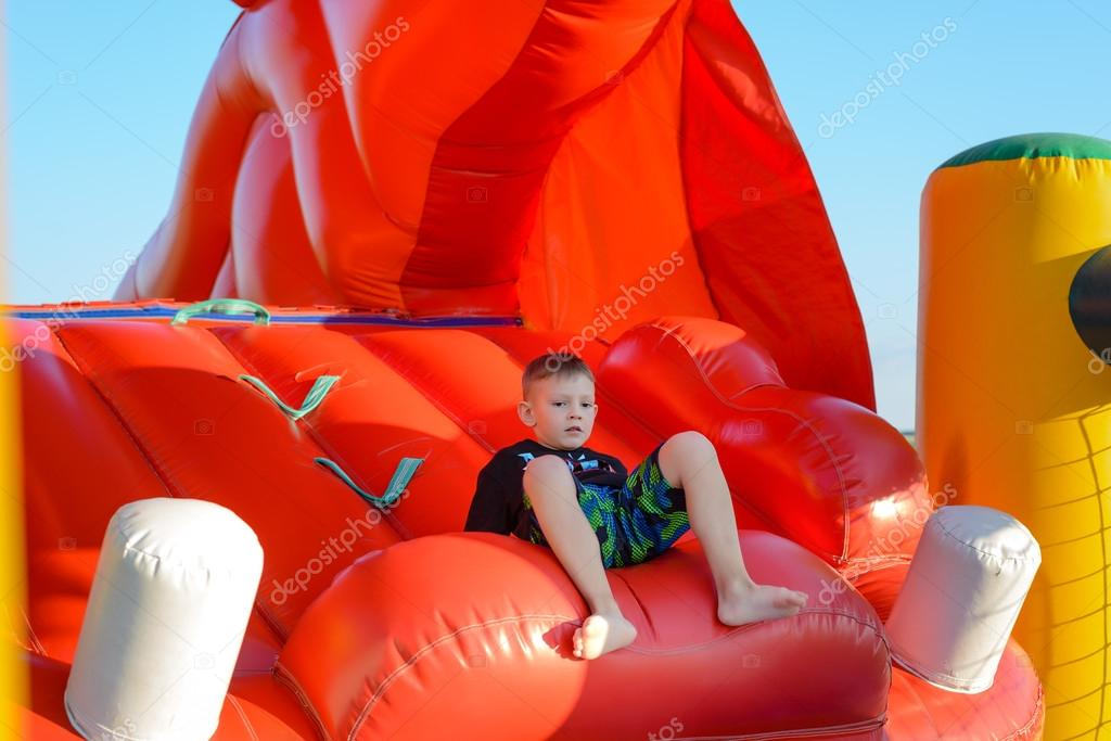 Blonde boy (7-9 years) sitting in bouncy castle