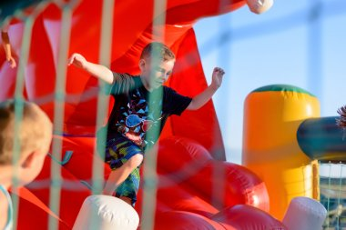 Small boy playing on bouncy castle