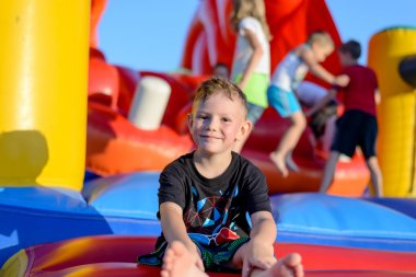 Smiling little boy sitting on a jumping castle