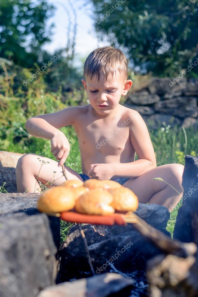 Topless Boy Grilling Bread and Sausages on Sticks