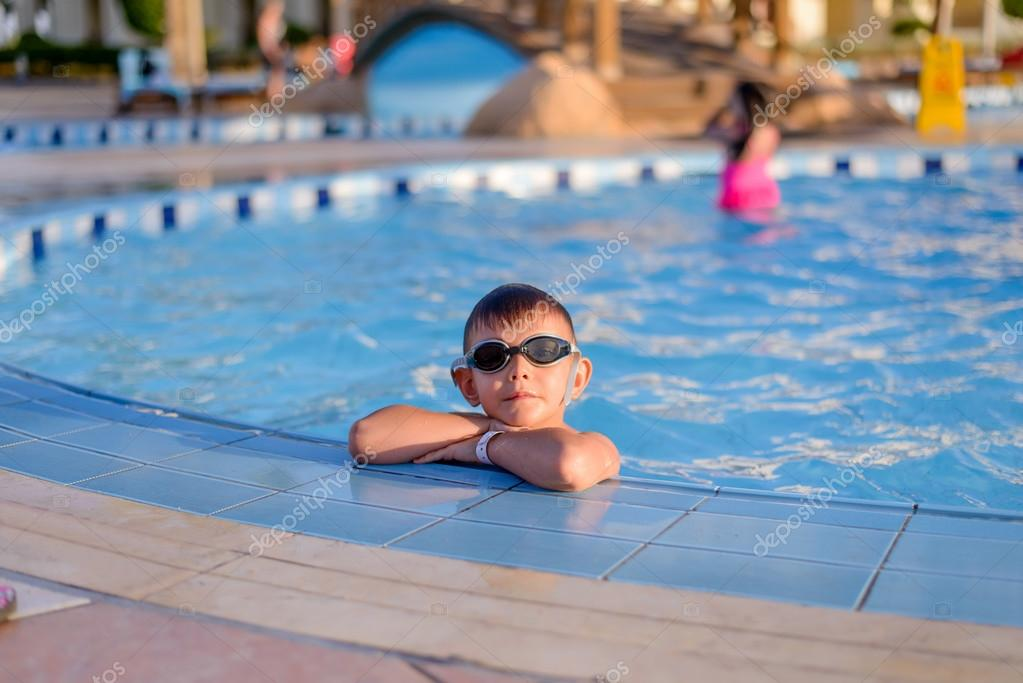 Young boy sitting at the side of a pool