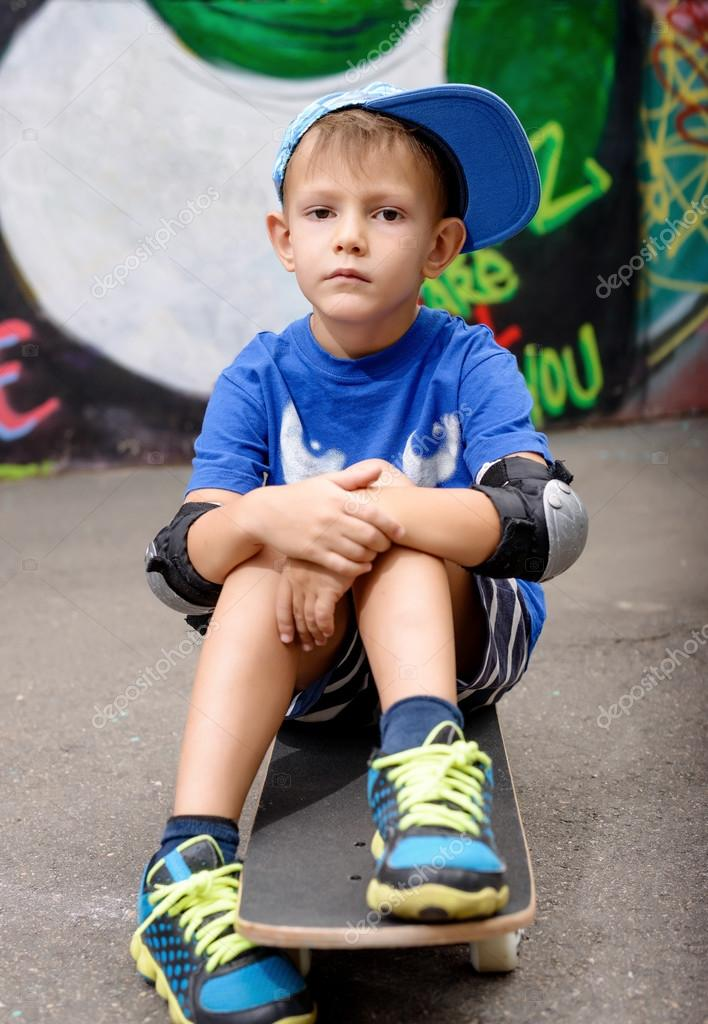 Portrait of Young Boy Sitting on Skateboard