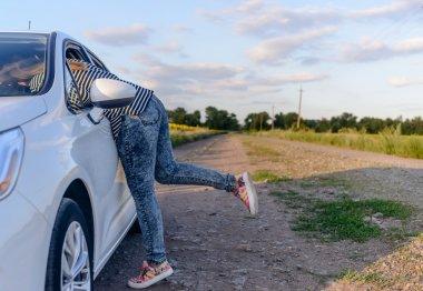 Woman reaching inside the open window of a car