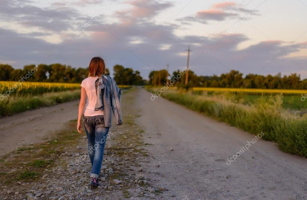 Woman walking down a country road
