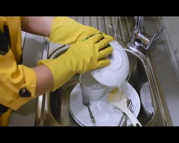 Žena v gumových rukavicích myje nádobí v kuchyňském dřezu, jen ruce