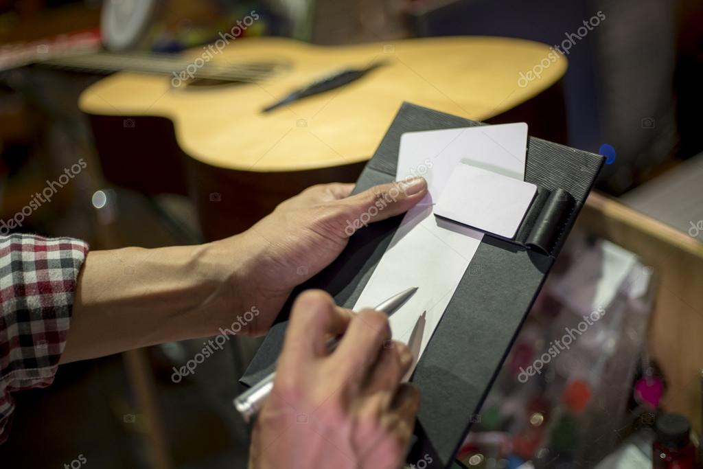 d7001c04b2343f Klant ondertekening op verkoop slip accepteren om te kopen gitaar —  Stockfoto