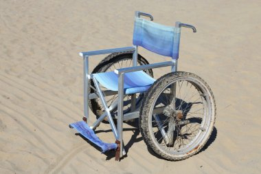isolated wheelchair made of aluminum on beach sand