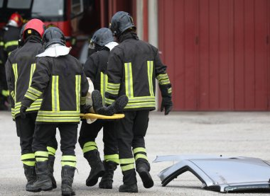 Bir grup itfaiyeci kazadan sonra yaralıları sedyeyle kurtarırken...