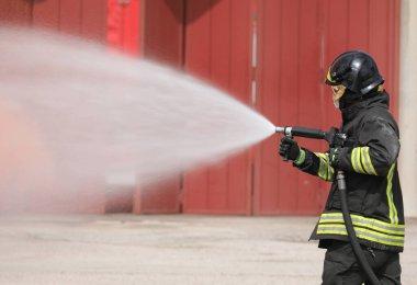 Kasklı ve üniformalı cesur itfaiyeci özel bir alev geciktirici köpükle araba yangınını söndürüyor.
