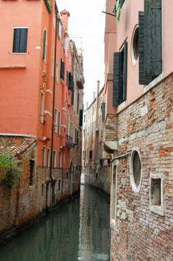 narrow navigable canal between the tall houses of Venice in Ital