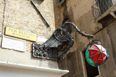 signs to Rialto Bridge with the bronze statue of a dragon and a