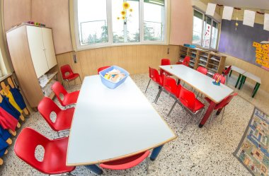 Classroom nursery with red chairs and desks for children