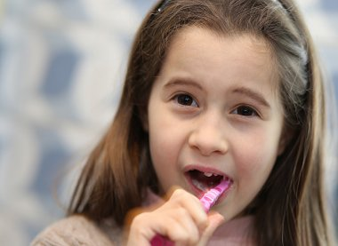 young girl without a tooth while brushing teeth in the bathroom
