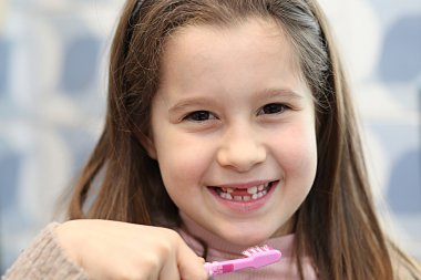 young girl without a tooth while brushing teeth