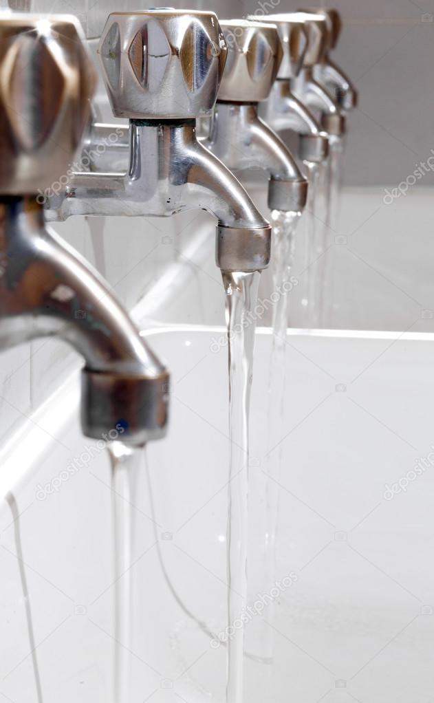 steel taps with drinking water flowing in college bathroom