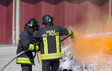 two firefighters in action with foam