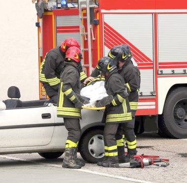 İtalyan itfaiyeciler yaralı bir araba kazasından sonra rahatlatmak