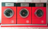 Fotografia tre rossi lavatrici in lavanderia a gettoni