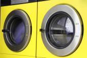 Fotografia due gialli lavatrici in lavanderie