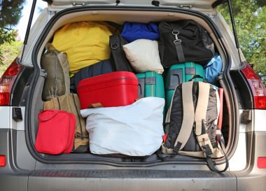 Car overloaded with suitcases for family travel