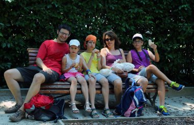 happy family of five people eat sandwiches on a bench