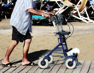 elderly man walking with Walker on the beach