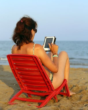 tanned woman reads the ebook on the beach