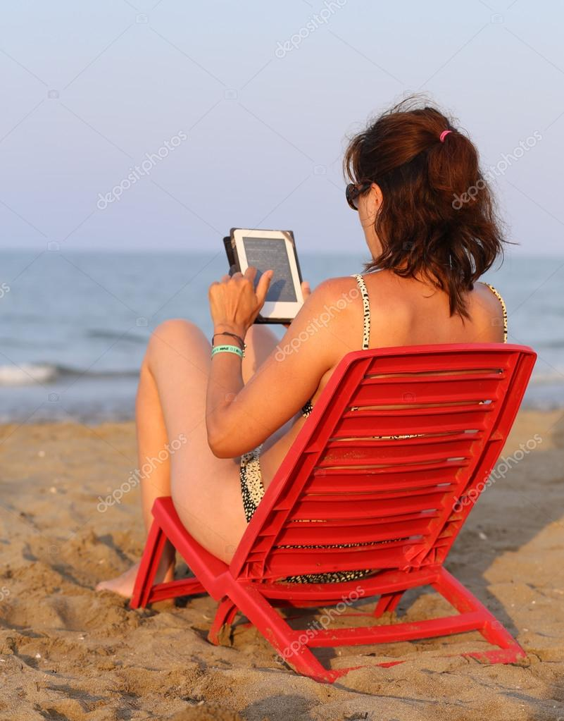 tanned woman reads the ebook on the seashore i