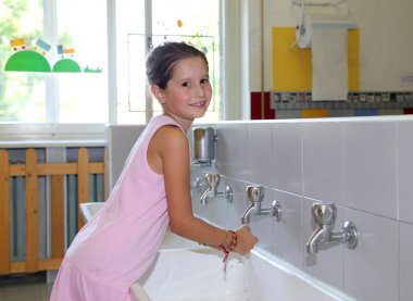 little girl washing hands in the ceramic sink in the bathroom  o