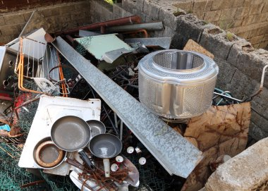 old pans and washing machine basket in waste landfill