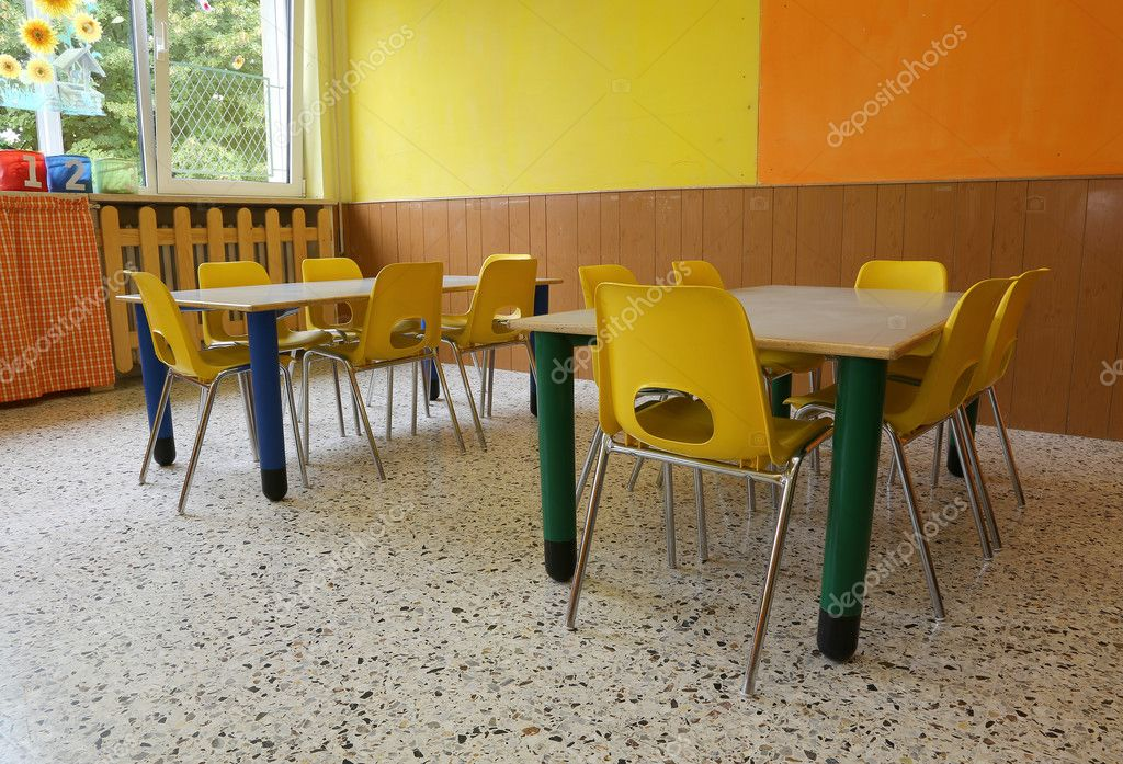 Sedie Pieghevoli Gialle : Aula di scuola materna con scrivanie e sedie gialle senza bambini