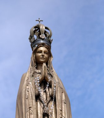 statue of our Lady with clasped hands and the precious Crown