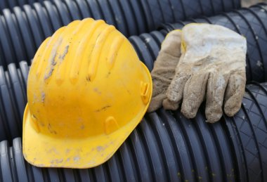 yellow hard hat and work gloves in construction site