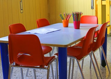 kindergarten with red chairs and small desks and lots of colored