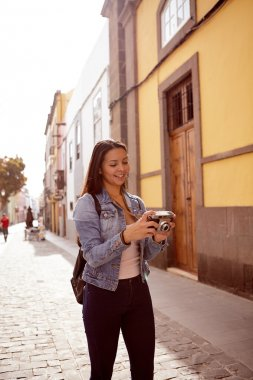woman walking in city with camera