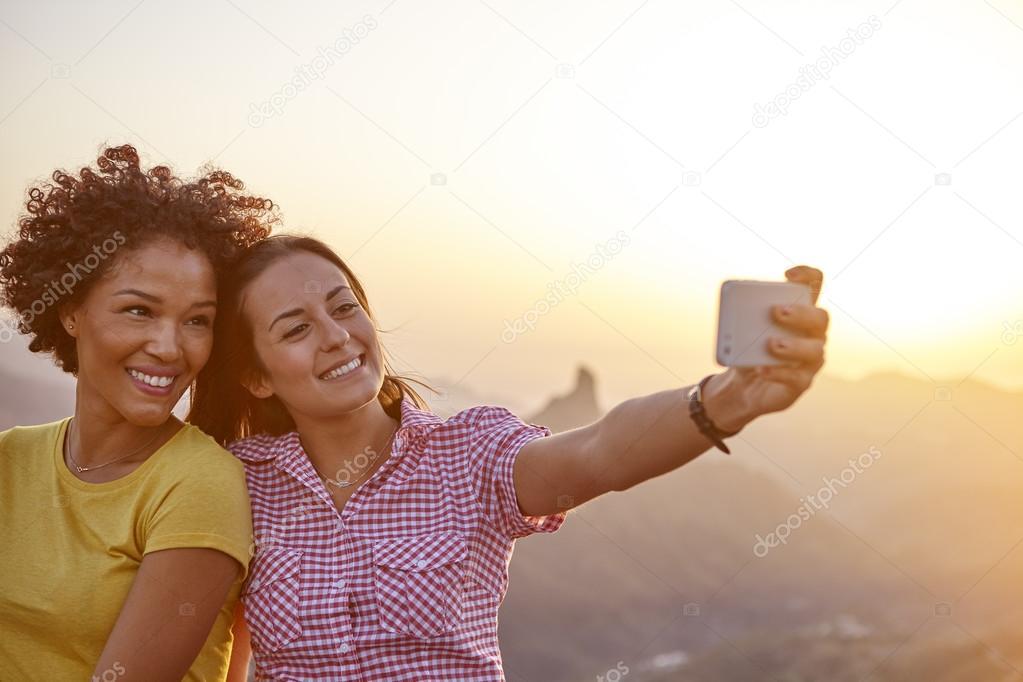 Girl friends taking selfie in mountains