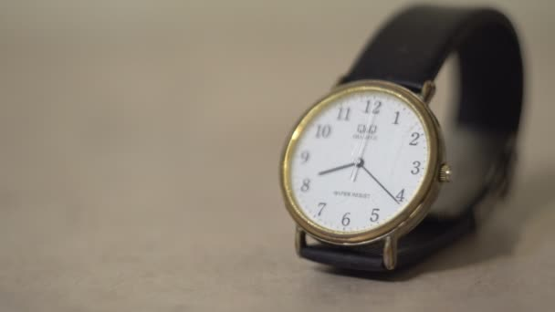 Quartz wrist watch. White dial. Black arrows. The strap is black. Black numbers. Close-up.