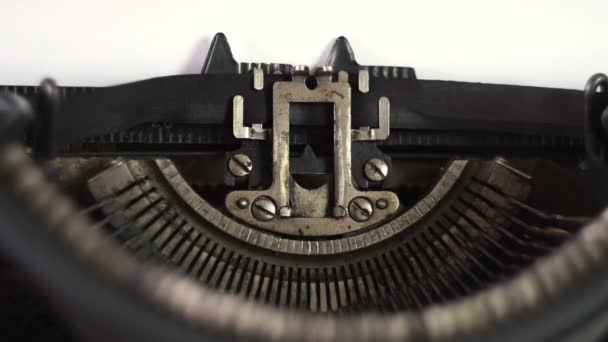 The mechanism of an old typewriter. The text is printed. Printed tape. Metal letters. A sheet of white paper. Close-up. Macro view.