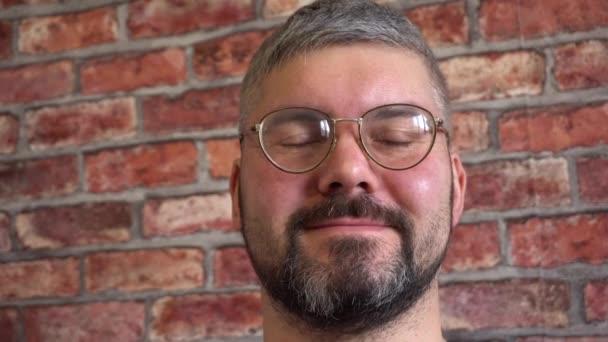 Vertikální video. Vousáč v kulatých brýlích. Vypadá rovně. Krátký sestřih. Modré tričko. Špatný zrak. Na pozadí cihlové zdi. Detailní záběr.