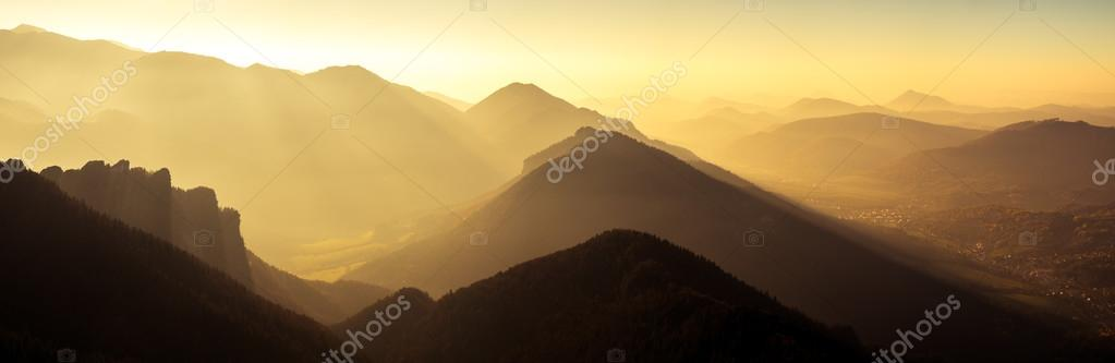 Panoramic scenic view of mountains and hills silhouette at sunse