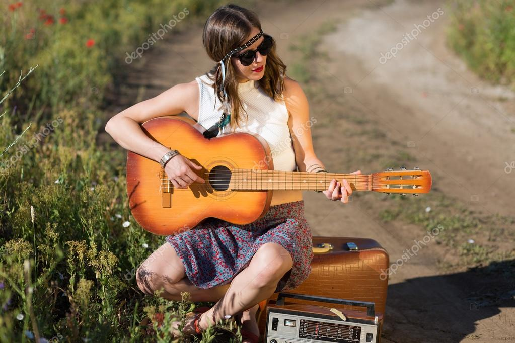 Beautiful woman with a suitcase and a guitar