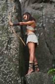 Fotografie Primitive Frau, die auf einem Felsen stehend und halten einen Bogen. Amazon-Frau